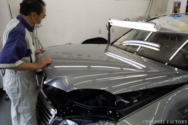 小山薫堂さんの愛車、MercedesBenz E63 AMGステーションワゴンのボンネットの凹みを修復中の斎藤さん画像